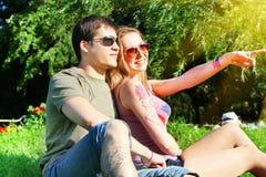Pares sonrientes jovenes en las gafas de sol que se sientan en un parque en día soleado amistad, ocio, concepto del verano Imágenes de archivo libres de regalías