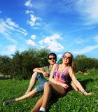 Pares sonrientes jovenes en las gafas de sol que se sientan en un parque en día soleado amistad, ocio, concepto del verano Fotos de archivo