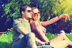 Pares sonrientes jovenes en las gafas de sol que se sientan en un parque en día soleado amistad, ocio, concepto del verano Foto de archivo libre de regalías