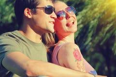 Pares sonrientes jovenes en las gafas de sol que se sientan en un parque en día soleado amistad, ocio, concepto del verano Fotografía de archivo