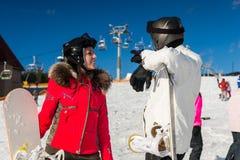Pares sonrientes jovenes en trajes de esquí, cascos y suplente de las gafas del esquí Foto de archivo