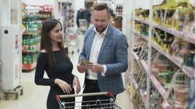 Pares sonrientes jovenes felices que eligen los ultramarinos y que hacen compras en supermercado almacen de metraje de vídeo