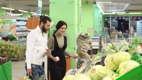 Pares sonrientes jovenes hermosos que eligen la cebolla en supermercado junto almacen de video