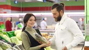 Pares sonrientes jovenes hermosos que eligen la coliflor en supermercado junto almacen de metraje de vídeo