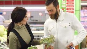 Pares sonrientes jovenes hermosos que eligen la coliflor en supermercado junto metrajes