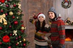 Pares sonrientes jovenes que adornan el árbol de navidad en su r vivo Imagen de archivo