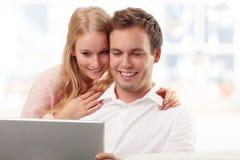 Pares sonrientes jovenes que compran en Internet Fotos de archivo