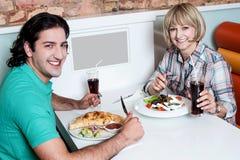 Pares sonrientes jovenes que disfrutan de comidas fotografía de archivo