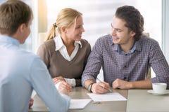 Pares sonrientes jovenes que firman un préstamo imagenes de archivo