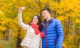 Pares sonrientes que abrazan en parque del otoño Imagen de archivo libre de regalías