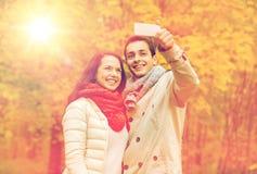 Pares sonrientes que abrazan en parque del otoño Fotos de archivo