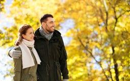 Pares sonrientes que abrazan en parque del oto?o imagen de archivo