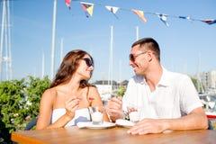 Pares sonrientes que comen el postre en el café Imagen de archivo
