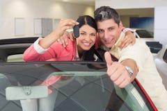 Pares sonrientes que dan los pulgares para arriba y llevar a cabo llave del coche Imagen de archivo libre de regalías