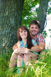 Pares sonrientes que descansan cerca de un árbol Fotografía de archivo libre de regalías
