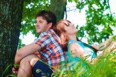 Pares sonrientes que descansan cerca de un árbol Fotos de archivo libres de regalías
