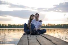 Pares sonrientes que descansan sobre el puente en la orilla del lago en la puesta del sol Imagen de archivo