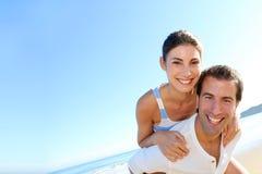 Pares sonrientes que disfrutan de vacaciones de verano en la playa Imagenes de archivo