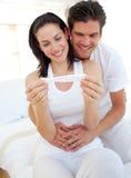 Pares sonrientes que encuentran resultados de la prueba de embarazo Foto de archivo