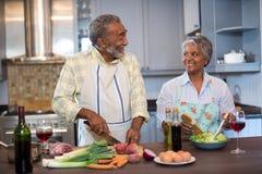 Pares sonrientes que hablan mientras que prepara la comida en casa imagen de archivo libre de regalías