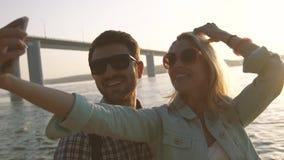 Pares sonrientes que hacen imágenes de ellos mismos contra fondo de la sol almacen de metraje de vídeo