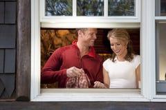 Pares sonrientes que hacen platos en la ventana de la cocina Imagenes de archivo