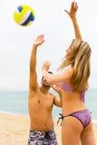 Pares sonrientes que juegan con una bola en la playa Imágenes de archivo libres de regalías