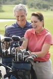 Pares sonrientes que juegan a golf Imágenes de archivo libres de regalías
