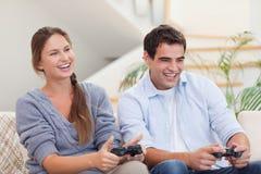 Pares sonrientes que juegan a los videojuegos Imágenes de archivo libres de regalías