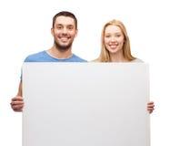 Pares sonrientes que llevan a cabo al tablero en blanco blanco Foto de archivo