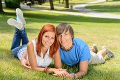 Pares sonrientes que mienten en el primer amor del parque Imagen de archivo libre de regalías