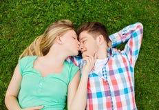 Pares sonrientes que mienten en hierba y que se besan en parque Fotos de archivo