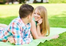 Pares sonrientes que mienten en la manta en parque Imagen de archivo libre de regalías