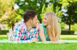 Pares sonrientes que mienten en la manta en parque Foto de archivo libre de regalías