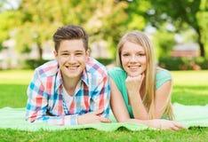 Pares sonrientes que mienten en la manta en parque Imagen de archivo