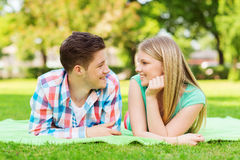 Pares sonrientes que mienten en la manta en parque Fotografía de archivo libre de regalías