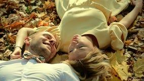 Pares sonrientes que mienten en parque del otoño almacen de metraje de vídeo