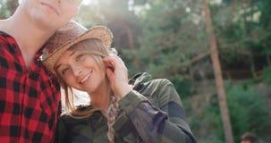 Pares sonrientes que miran la cámara mientras que se relaja en bosque Imagen de archivo libre de regalías