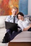 Pares sonrientes que miran la computadora portátil Fotografía de archivo libre de regalías