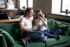 Pares sonrientes que miran la sentada en línea video móvil en el sofá casero Imagenes de archivo