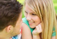 Pares sonrientes que miran uno a en parque Foto de archivo libre de regalías