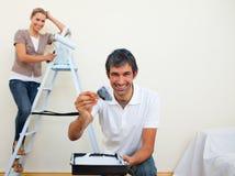 Pares sonrientes que pintan una pared Fotografía de archivo