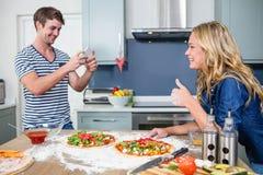 Pares sonrientes que preparan la pizza Imagen de archivo libre de regalías