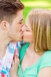 Pares sonrientes que se besan y que abrazan en parque Fotos de archivo libres de regalías