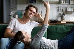 Pares sonrientes que se divierten con el smartphone que toma el selfie en casa Imagen de archivo