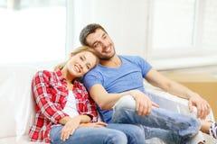 Pares sonrientes que se relajan en el sofá en nuevo hogar imágenes de archivo libres de regalías