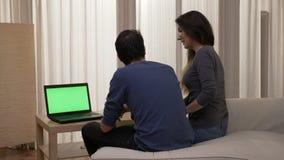 Pares sonrientes que se sientan al borde de la cama que mira un ordenador portátil con la pantalla verde mientras que teniendo un almacen de metraje de vídeo
