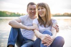 Pares sonrientes que se sientan en el puente en la orilla del lago en la puesta del sol Fotografía de archivo libre de regalías
