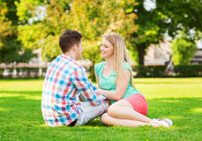 Pares sonrientes que se sientan en hierba en parque Fotografía de archivo