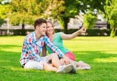 Pares sonrientes que se sientan en hierba en parque Imagen de archivo libre de regalías